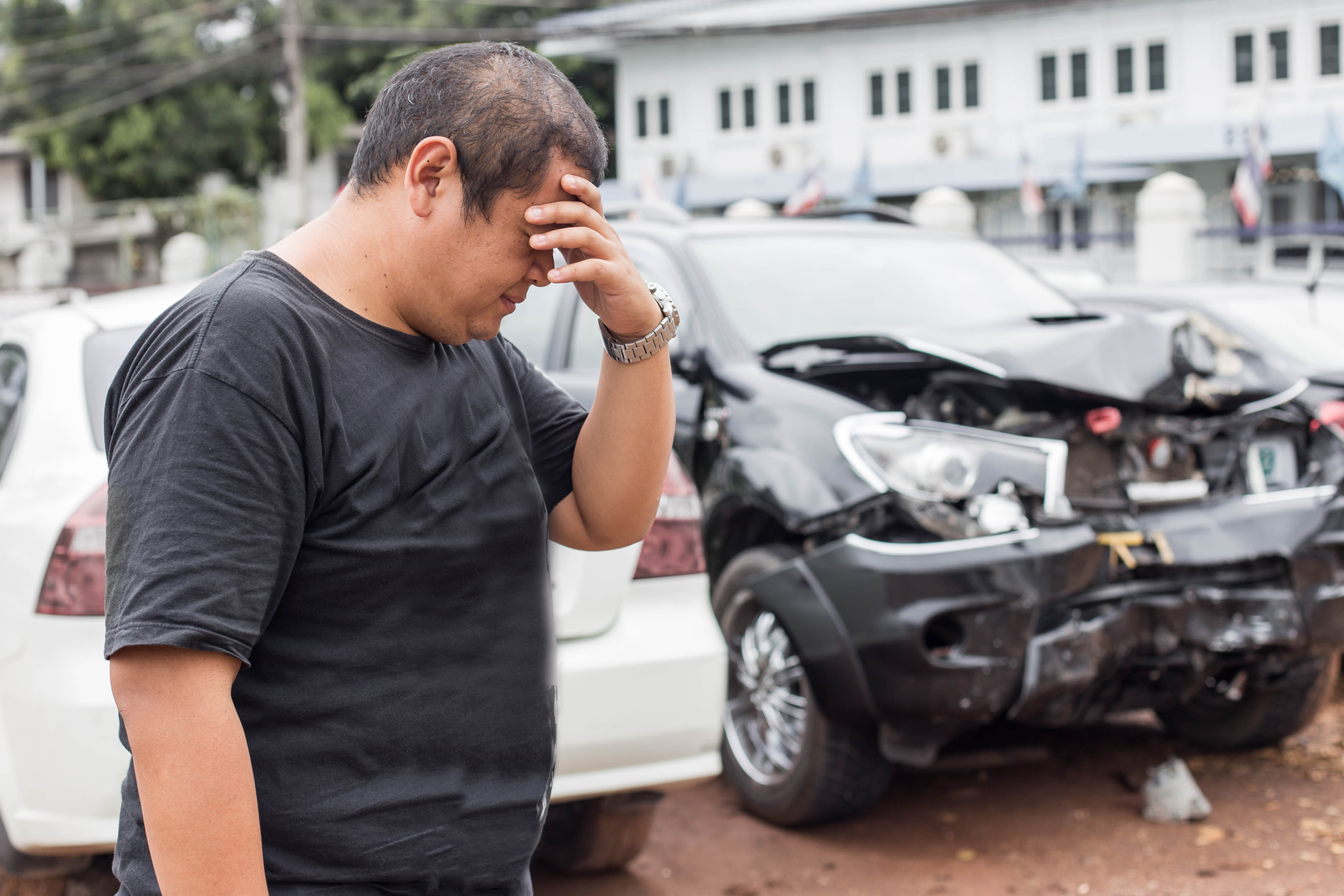 man standing in front of a wrecked car before he calls a car accident lawyer